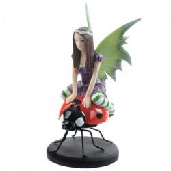 Cette figurine représente une Fée de collection assise sur une coccinelle géante