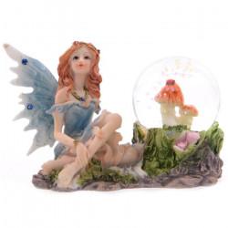 Figurine de Fée assise à côté d'une boule à neige